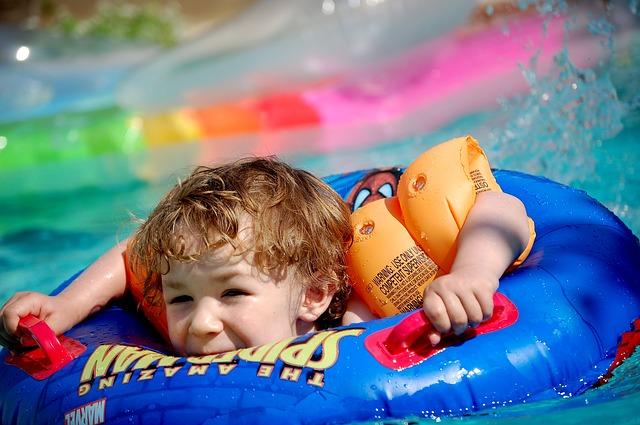 Dítě v bazénu v modrém plovacím kruhu se spidermanem a s barevnými oranžovými rukávky