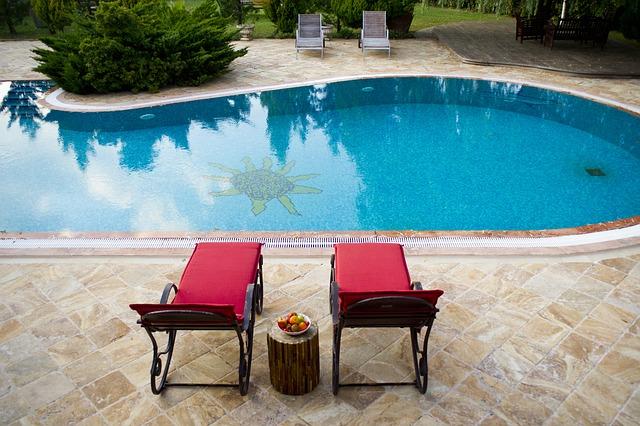 Vydlážděná terasa s bazénem, ve kterém je na zemi namalované slunce a se dvěma červenými křesly na sezení v popředí