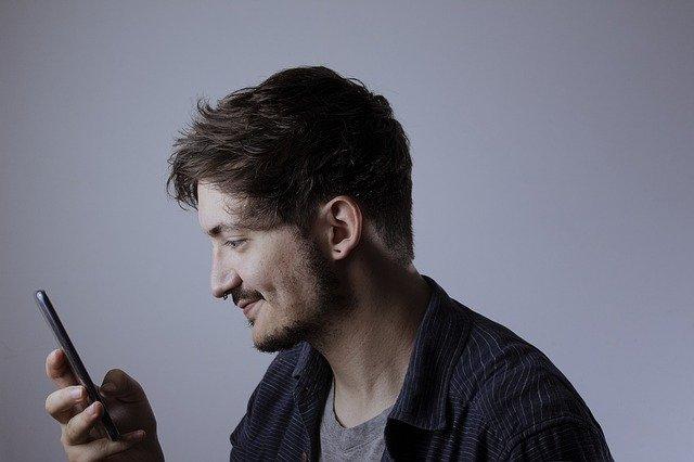 muž smějící se u telefonu